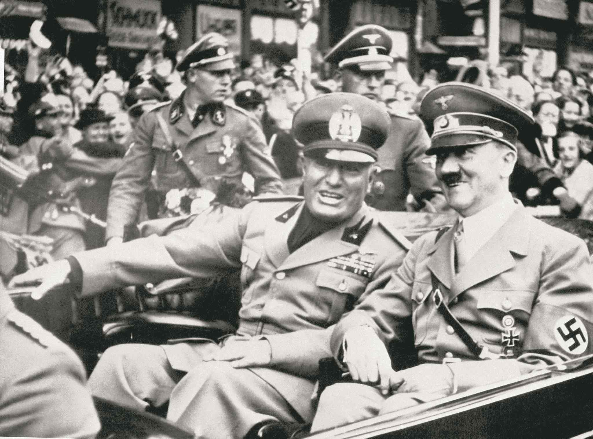 In this Sept. 28, 1938, photo, Italian dictator Benito Mussolini (left) and Adolf Hitler take a ride before a conference in Munich, Germany.