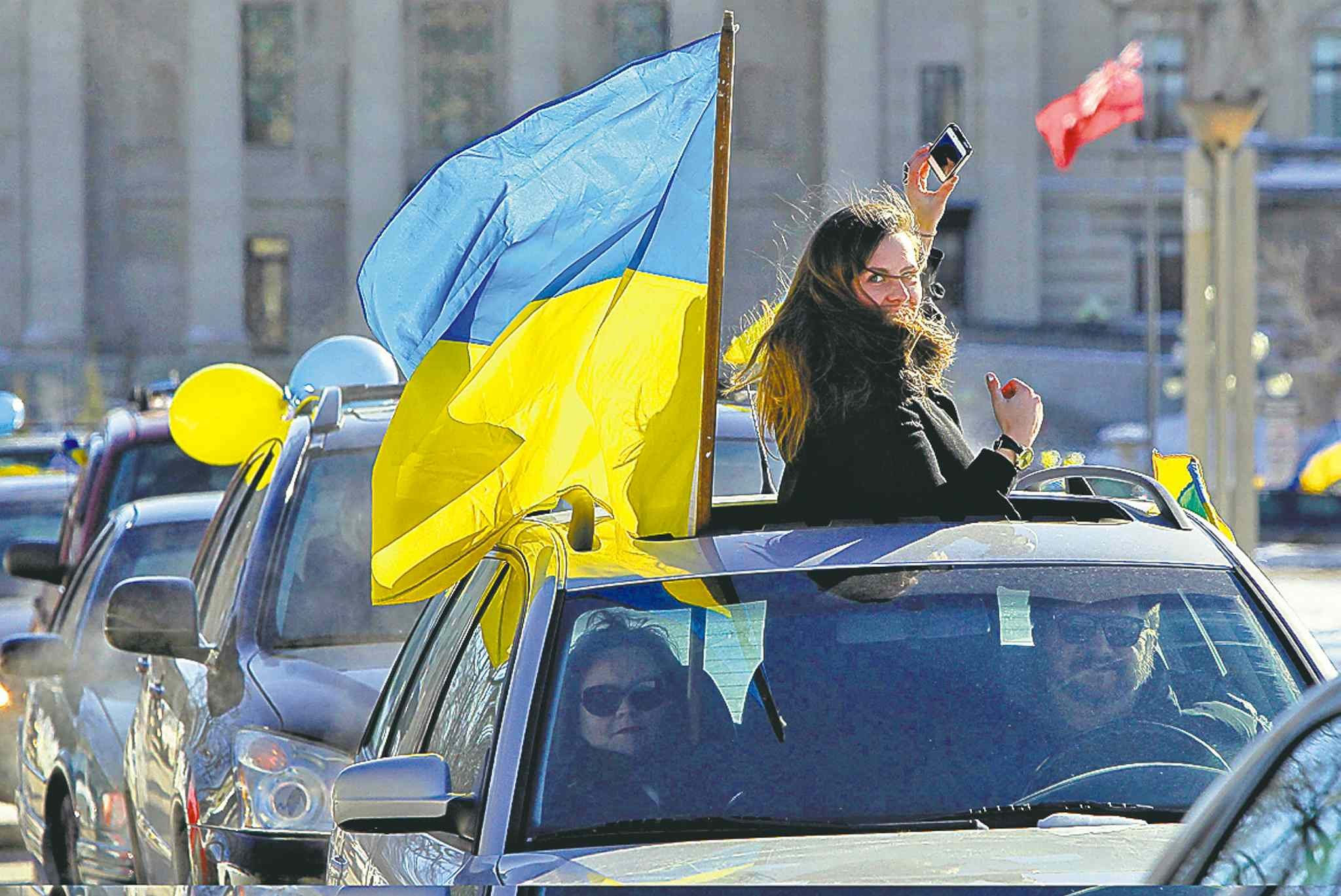 Daria Lytwyn tries to get a quick photo of the procession while taking part in a car rally in Winnipeg Sunday.