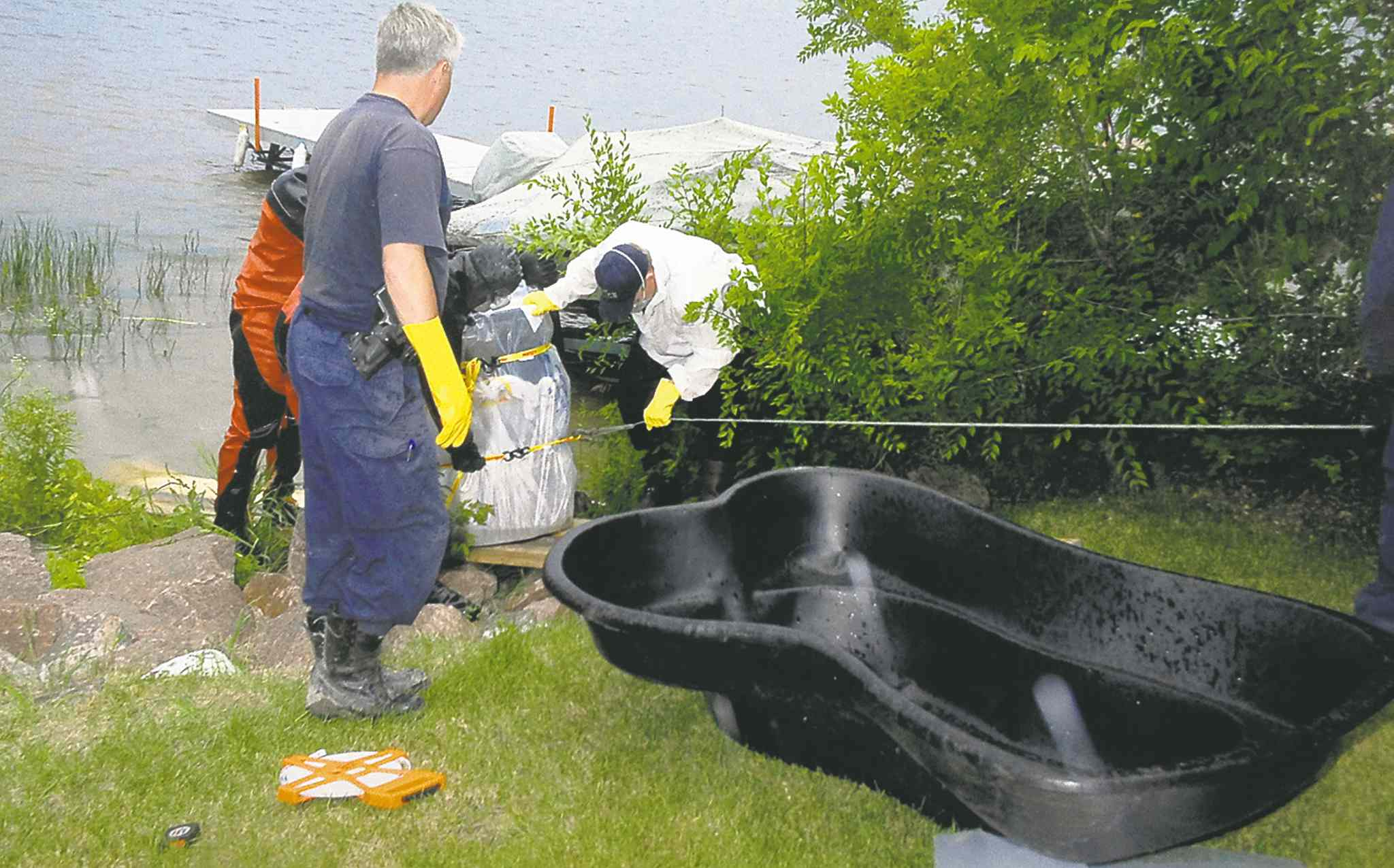 RCMP / Manitoba Justice RCMP divers and forensic officers secure the barrel in which the body of Chad Davis (at right) was found in 2008.