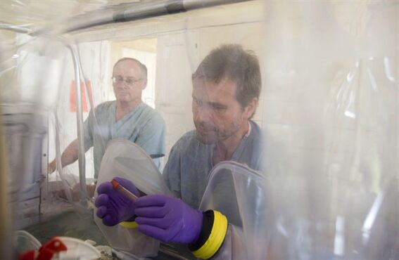 Heinz Feldmann, right, and Allen Grolla, left, work in a mobile laboratory installed by specialists of the National Public Health Agency of Canada, which enables teams on the ground to conduct rapid and precise diagnosis of new suspected Ebola cases and other diseases, within two to six hours, in Mweka, Congo, Friday, Sept. 28, 2007. THE CANADIAN PRESS/AP Photo/WHO, Christopher Black, HO) ** EDITORIAL USE ONLY **