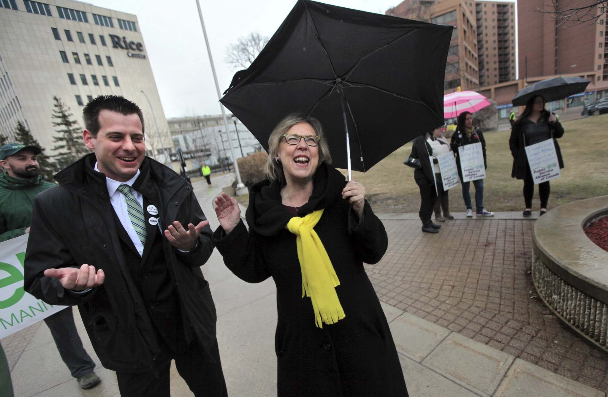 PHIL HOSSACK / WINNIPEG FREE PRESS</p><p>Manitoba Green Party leader James Beddome and National Green Party leader Elizabeth May share a laugh despite the rain at a rally for a $15 minimum wage that gathered at the Univercity of Winnipeg Friday at noon before marching down Portage Avenue.</p>