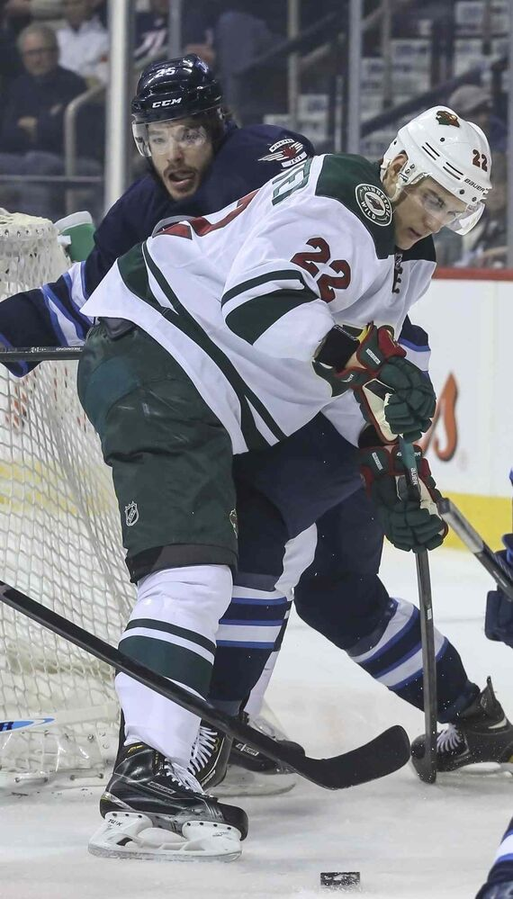 Jets defenceman Zach Redmond battles for the puck with the Wild's Nino Niederreiter in the Jets' zone during the first period. (CRYSTAL SCHICK / WINNIPEG FREE PRESS)