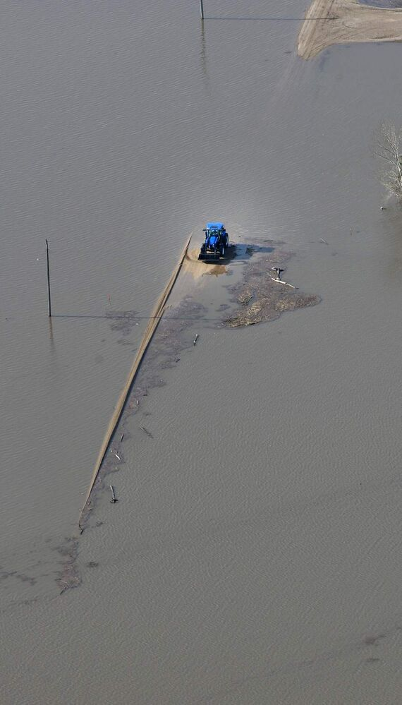 A farmer tractor sits on a submerged country road caused by the flooding Red River between the towns of St Jean Baptiste and Morris. JOE BRYKSA/WINNIPEG FREE PRESS