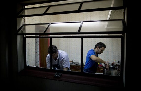In this April 12, 2014, photo, Chefs Martin Arrojo, left, and Ezequiel De La Torre prepare a meal for customers at their home in Buenos Aires, Argentina, Saturday, April 12, 2014. The website www.cookapp.com was launched in March 2013 and recently moved its headquarters from Buenos Aires to New York City. It works like a matchmaker, arranging intimate gourmet dinners between strangers. Chefs list when and where they will prepare particular meals; diners book what interests them, pay upfront via the app, then just show up and enjoy. (AP Photo/Natacha Pisarenko)