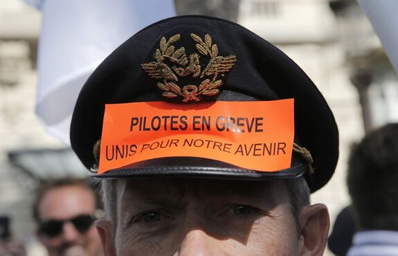 Air France pilots attend a demonstration in Paris, Tuesday, Sept. 23, 2014. France's prime minister speaking out against Air France pilots who are striking for an eighth day over the proposed expansion of its low-cost carrier, Transavia. Air France-KLM airline says the strike is costing up to euro20 million ($25 million) a day. The company is cutting costs to try to stay competitive with budget airlines. About half the airline's flights have been cancelled. The sticker reads: Pilots on strike. All together for our future. (AP Photo/Christophe Ena)