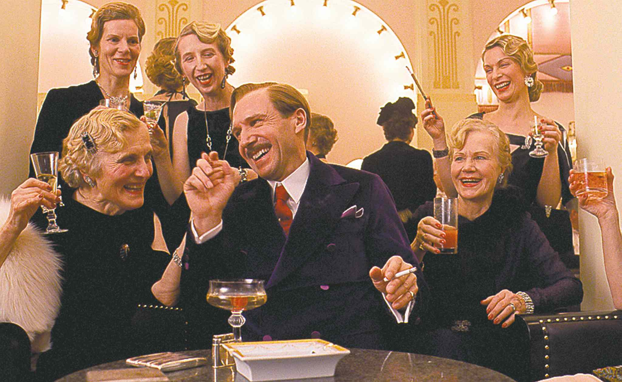 Ralph Fiennes, as M. Gustave, romances guests at the Grand Budapest Hotel.