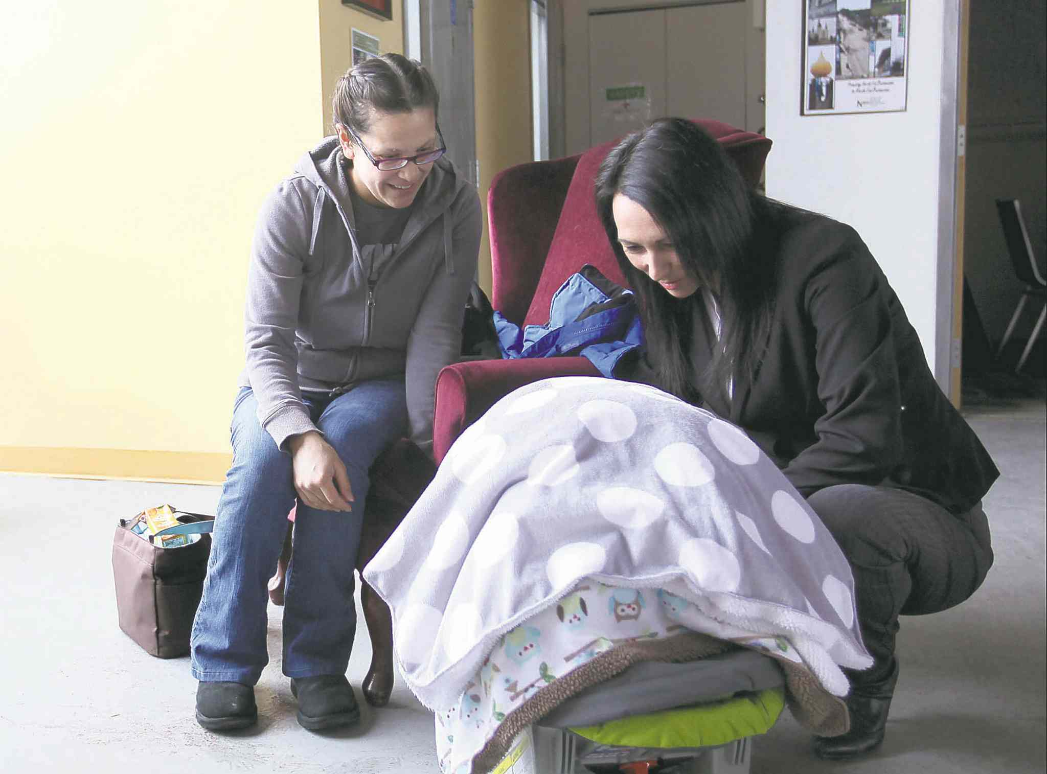 Proud mother Wendy Hallgrimson (left) shows baby son Lindal to  Diane Roussin in the Boldness Project offices on Selkirk Avenue.