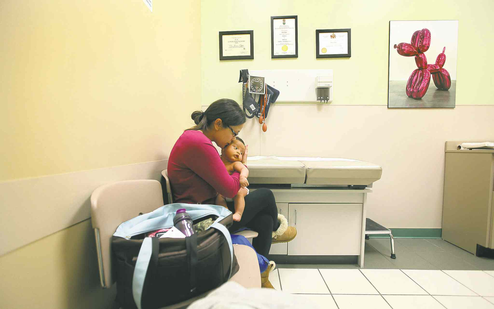 Wendy Hallgrimson cuddles Lindal at her pediatrician's office, where the baby will get his first immunization shots and a check up.