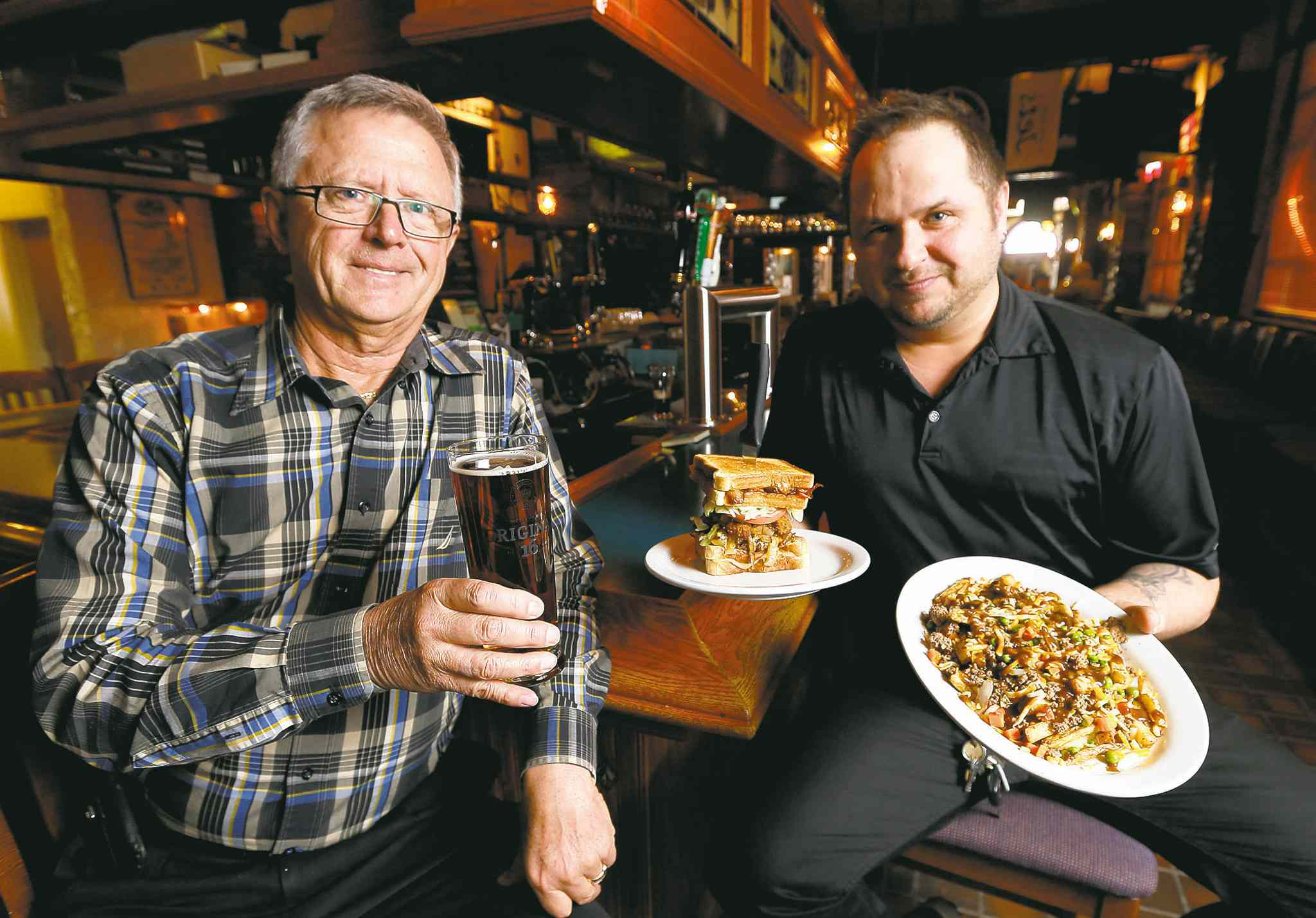 Owner Lawrence Maksymetz (left) and manager Lee Poworoznik, who is holding the shepherd's poutine and wolf hound burger, at the Fox & Hounds tavern at the St. James Hotel at 1719 Portage Ave.