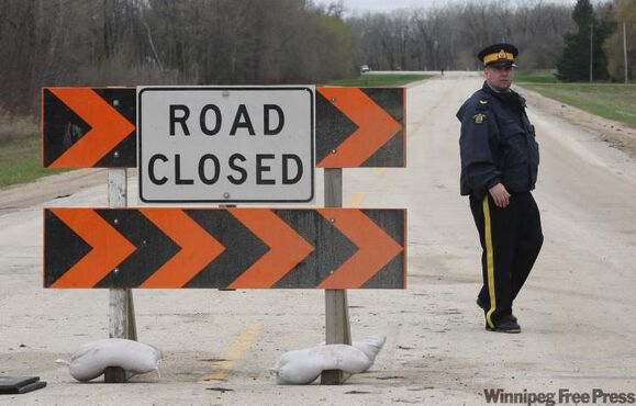 RCMP patrol a roadblock on Highway 331 near Hoop and Holler Bend on Wednesday.