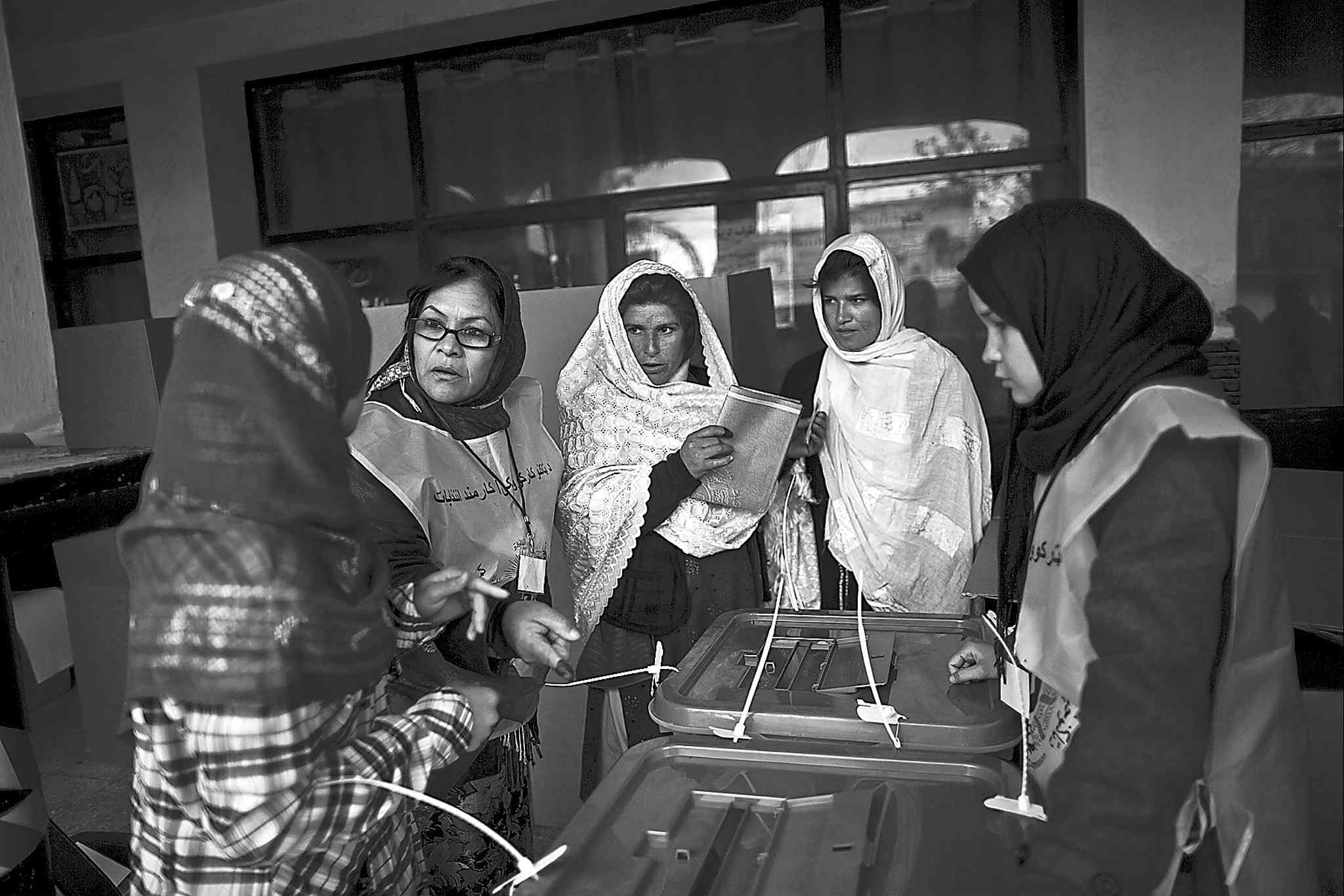 An Afghan election worker (second left) explains the process of elections on Saturday in Kabul.