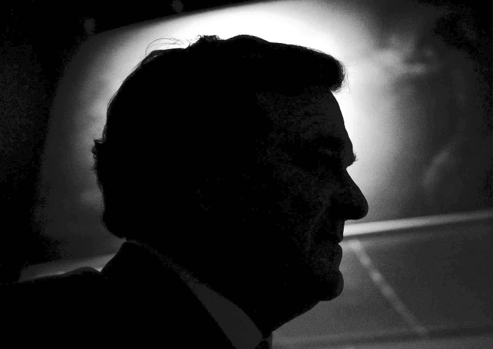 Former finance minister Jim Flaherty is silhouetted during an event at the Canadian War Museum in Ottawa in January 2012.