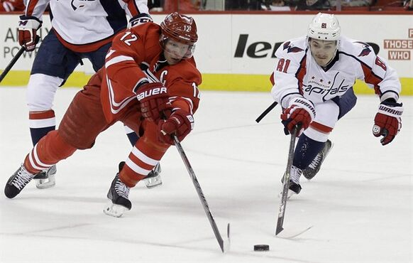 Carolina Hurricanes' Eric Staal (12) and Washington Capitals' Dmitry Orlov (81), of Russia, chase the puck during the second period of an NHL hockey game in Raleigh, N.C., Thursday, April 10, 2014. THE CANADIAN PRESS/AP/Gerry Broome