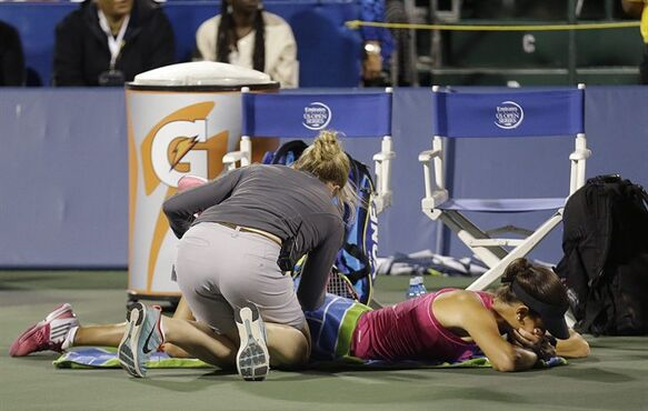 Ana Ivanovic, from Serbia, bottom, is tended to by a trainer during the second set of her match against Serena Williams in the Bank of the West Classic tennis tournament in Stanford, Calif., Friday, Aug. 1, 2014. Williams won 2-6, 6-3, 7-5. (AP Photo/Jeff Chiu)
