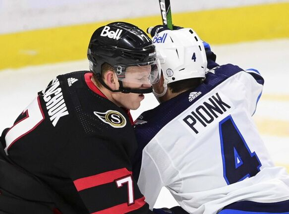 Ottawa Senators left wing Brady Tkachuk (7) and Winnipeg Jets defenceman Neal Pionk (4) battle in front of the net during second period NHL action in Ottawa on Tuesday, Jan. 19, 2021. THE CANADIAN PRESS/Sean Kilpatrick</p>