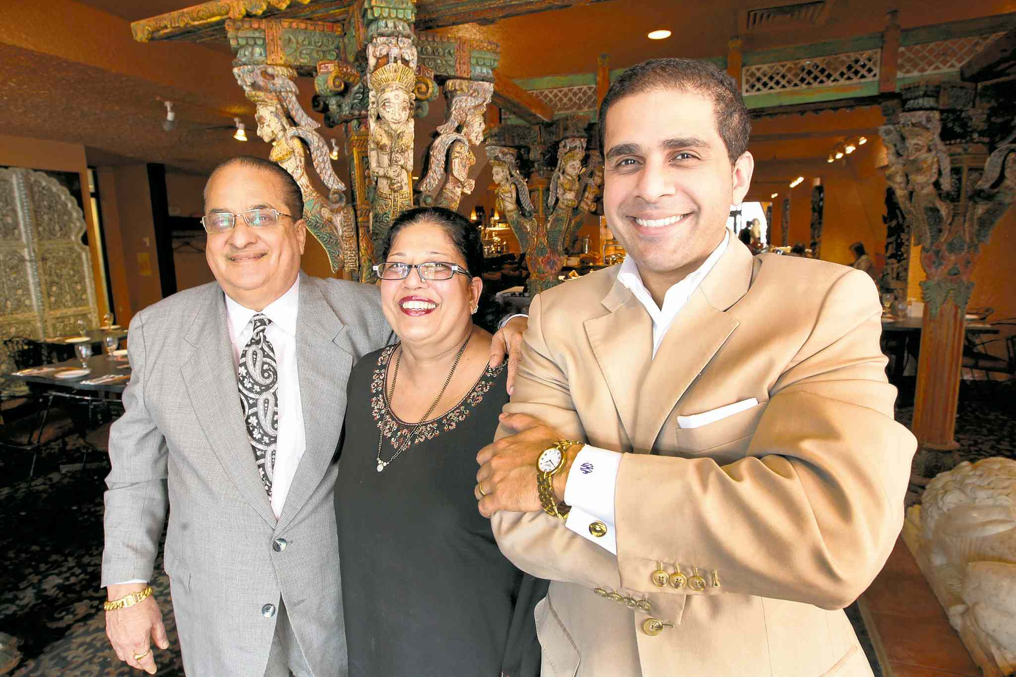 Sachit Mehra (right) with his father Kamal (left and) mother Sudha at the family's East India Company Pub & Eatery restaurant. Sachit is considering running for city council in St. Norbert.