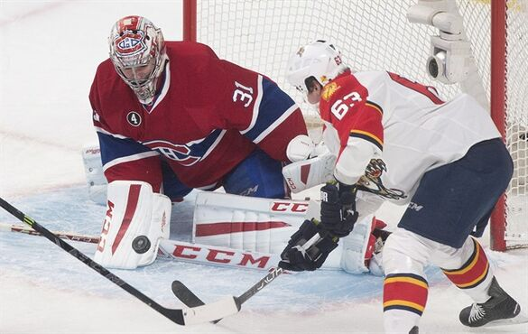 Montreal Canadiens goaltender Carey Price makes a save on Florida Panthers' Dave Bolland during first period NHL hockey action in Montreal, Saturday, March 28, 2015. There was a sigh of relief at the Montreal Canadiens practice rink when goalie Carey Price skated out and began his usual game day routine on Monday morning. THE CANADIAN PRESS/Graham Hughes