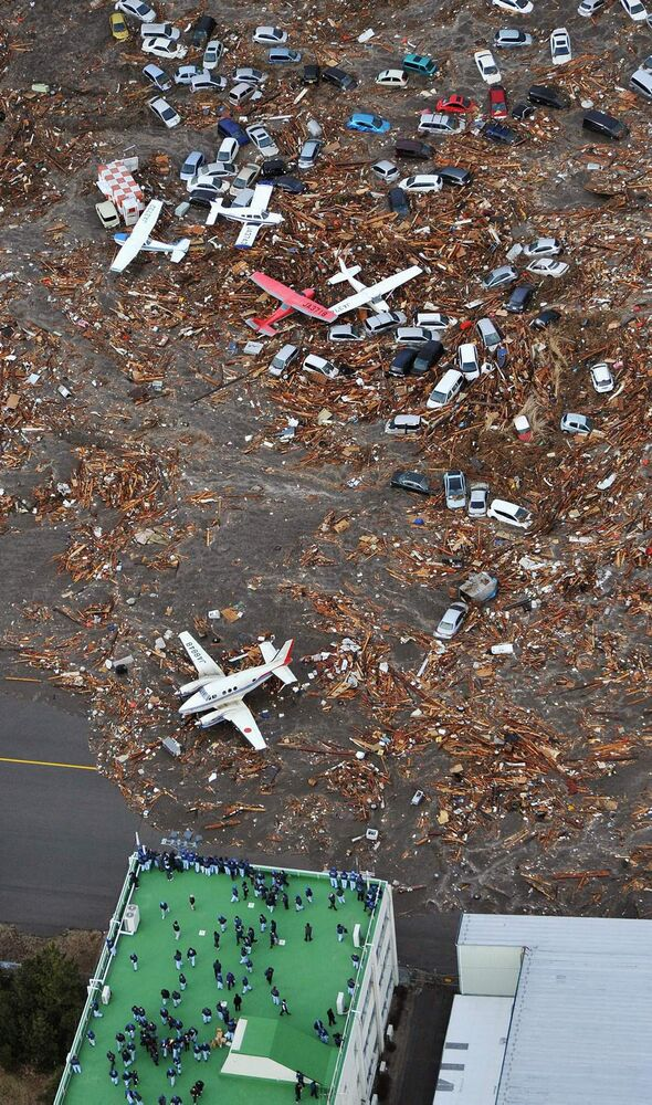 People seek refuge on the rooftop of a building as light planes and vehicles sit among the debris after they were swept by a tsumani that struck Sendai airport in northern Japan on Friday March 11, 2011. A magnitude 8.9 earthquake slammed Japan's eastern coast Friday, unleashing a 13-foot (4-meter) tsunami that swept boats, cars, buildings and tons of debris miles inland.  (AP Photo/Kyodo News)