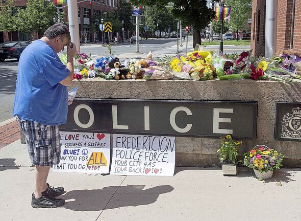 A man pauses by a display of flowers outside the police station in Fredericton on Friday, Aug. 10, 2018. Two city police officers were among four people who died in a shooting in a residential area on the city's north side.THE CANADIAN PRESS/Andrew Vaughan