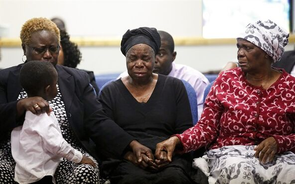 File - In the Oct. 18, 2014 file photo, Garteh Korkoryah, center, mother of Thomas Eric Duncan, is comforted during a memorial service for her son. It may not matter much that Texas Health Presbyterian Hospital Dallas apologized for initially misdiagnosing Duncan, who was sent home from the emergency room but later returned sicker and farther along on a painful decline to death from Ebola. Insulated by Texas tort reform that gives an extra layer of protection to emergency room doctors and nurses, not only is the very feasibility of winning a lawsuit complicated, but the potential payout is severely capped. (AP Photo/Nell Redmond, File)