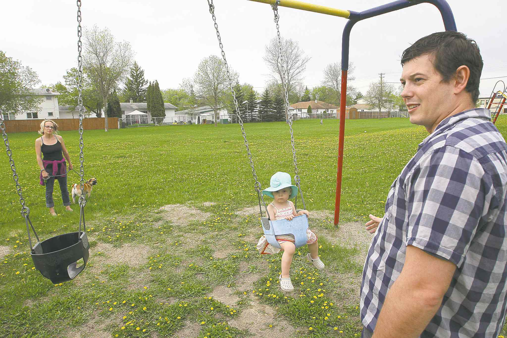 Dan Legge pushes his daughter, Audrey, on a swing in Voyageur Park on Thursday as he chats with neighbour Cindi Eastman.