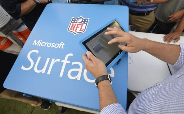 FILE - In this Aug. 3 2014 file photo, John Nisi, chief technology officer for Microsoft, works on a Surface tablet before the New York Giants play the Buffalo Bills at the Pro Football Hall of Fame exhibition NFL football game in Canton, Ohio. Microsoft reports quarterly financial results on Thursday, Oct. 23, 2014. (AP Photo/David Richard, File)