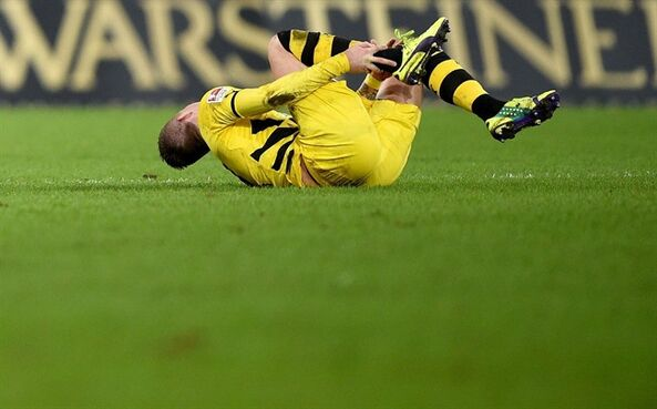 Dortmund's Marco Reus , lies injured on the ground during the German Bundesliga soccer match between SC Paderborn and Borussia Dortmund in Paderborn, Germany, Saturday Nov. 22, 2014. (AP Photo/dpa,Jonas Guettler)