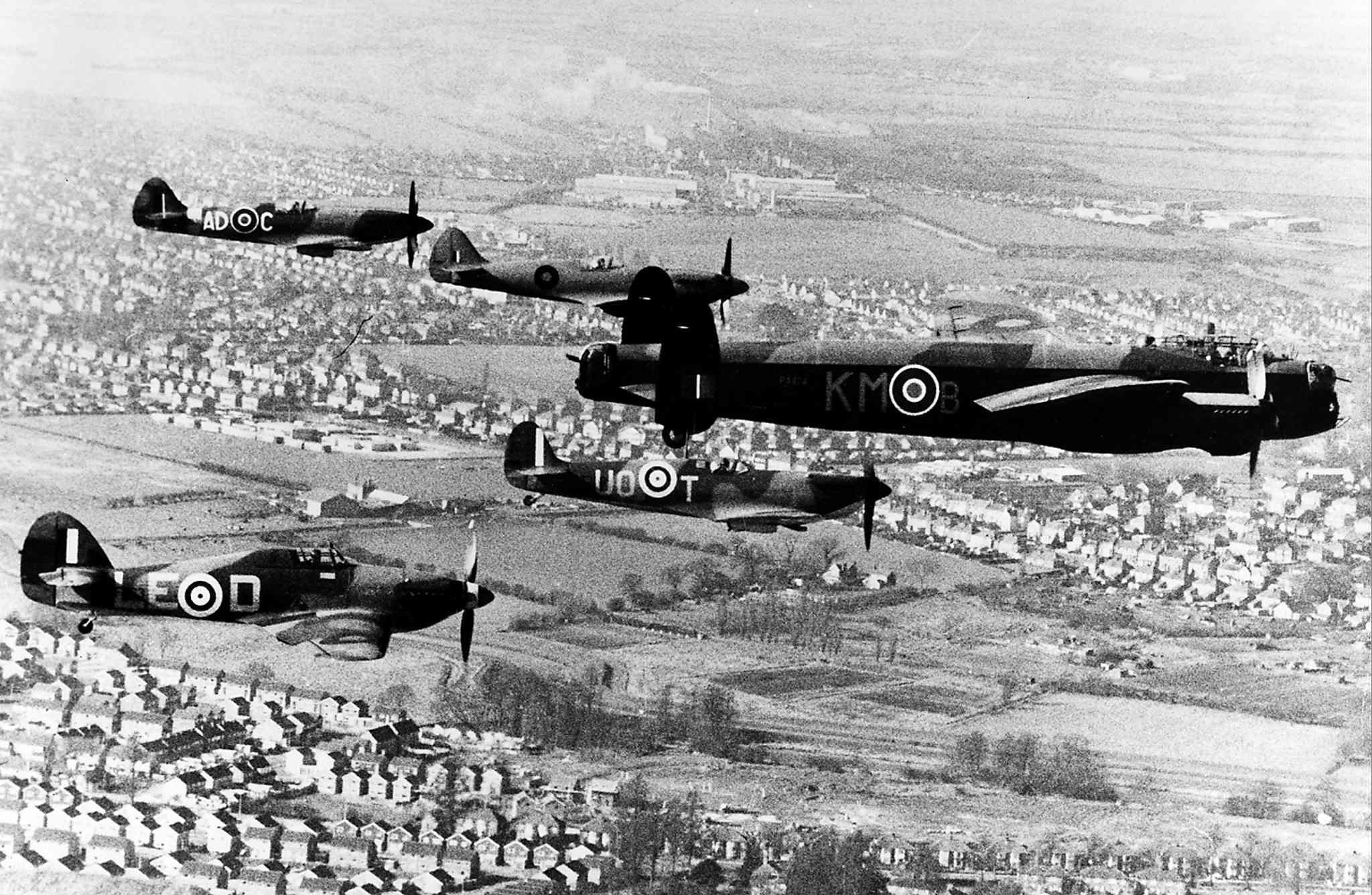 A Lancaster bomber leads a group of Second World War-era planes through British airspace.