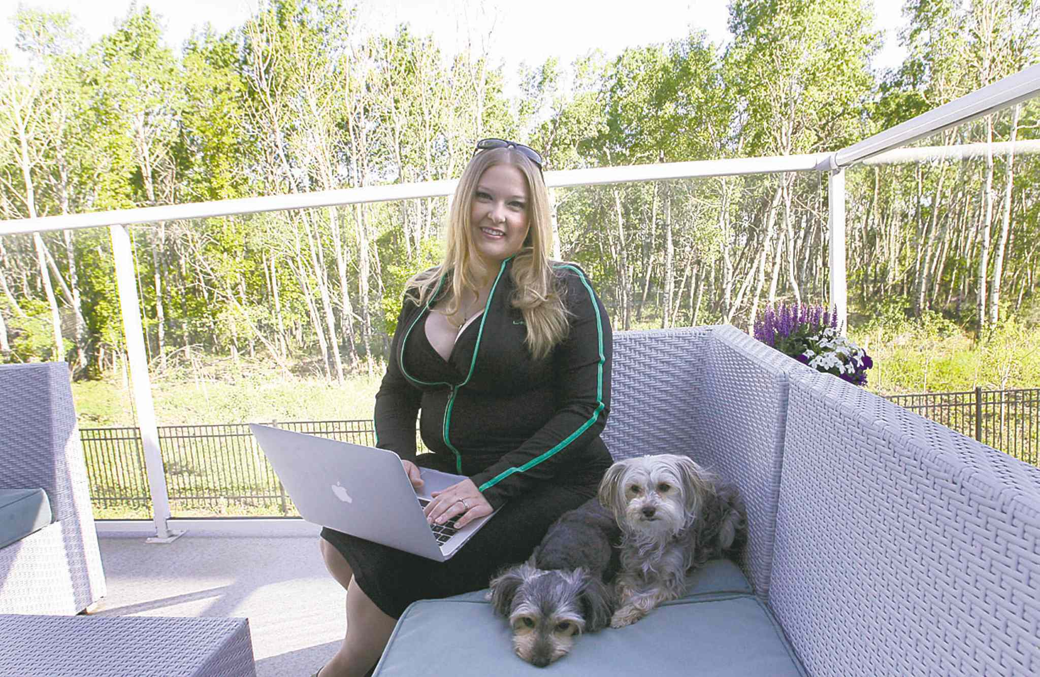 Tara Maltman-Just sits outside on her deck at home with her dogs, Calla and Lilly.