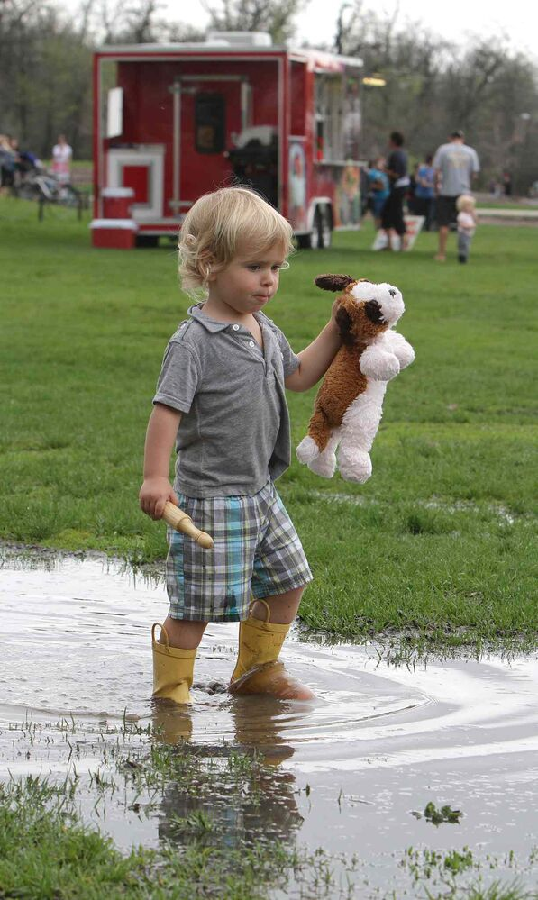 Dylan Gauthier, 3, walks through a puddle with his stuffed toy. (Jason Halstead / Winnipeg Free Press)