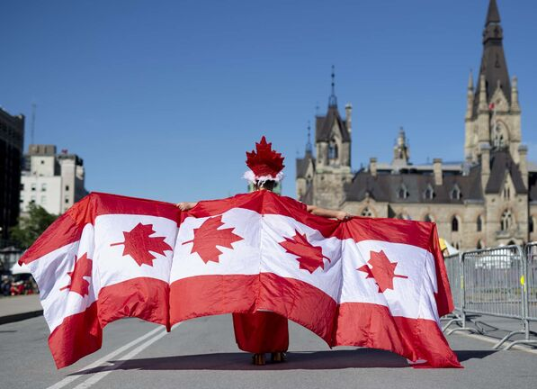 Andrew Larche wears an outfit made up of multiple Canadian flags as he walks on Parliament Hill in Ottawa on Canada Day in 2019. (Justin Tang / The Canadian Press)