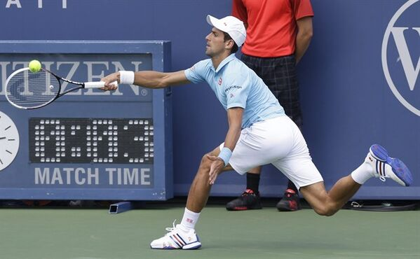 Novak Djokovic, from Serbia, returns a serve against Tommy Robredo, from Spain, during a match at the Western & Southern Open tennis tournament, Thursday, Aug. 14, 2014, in Mason, Ohio. (AP Photo/Al Behrman)