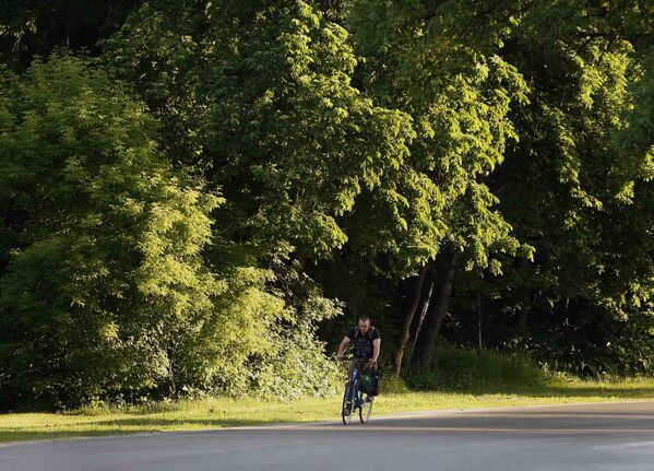 Stdup Weather  High +29 with a chance of a thunderstorm , a cyclist  rides on Wellington Cres. on as a bright sun start s to rise along the tree lined drive on a  Thursday morning  KEN GIGLIOTTI / JUNE 20 2013 / WINNIPEG FREE PRESS