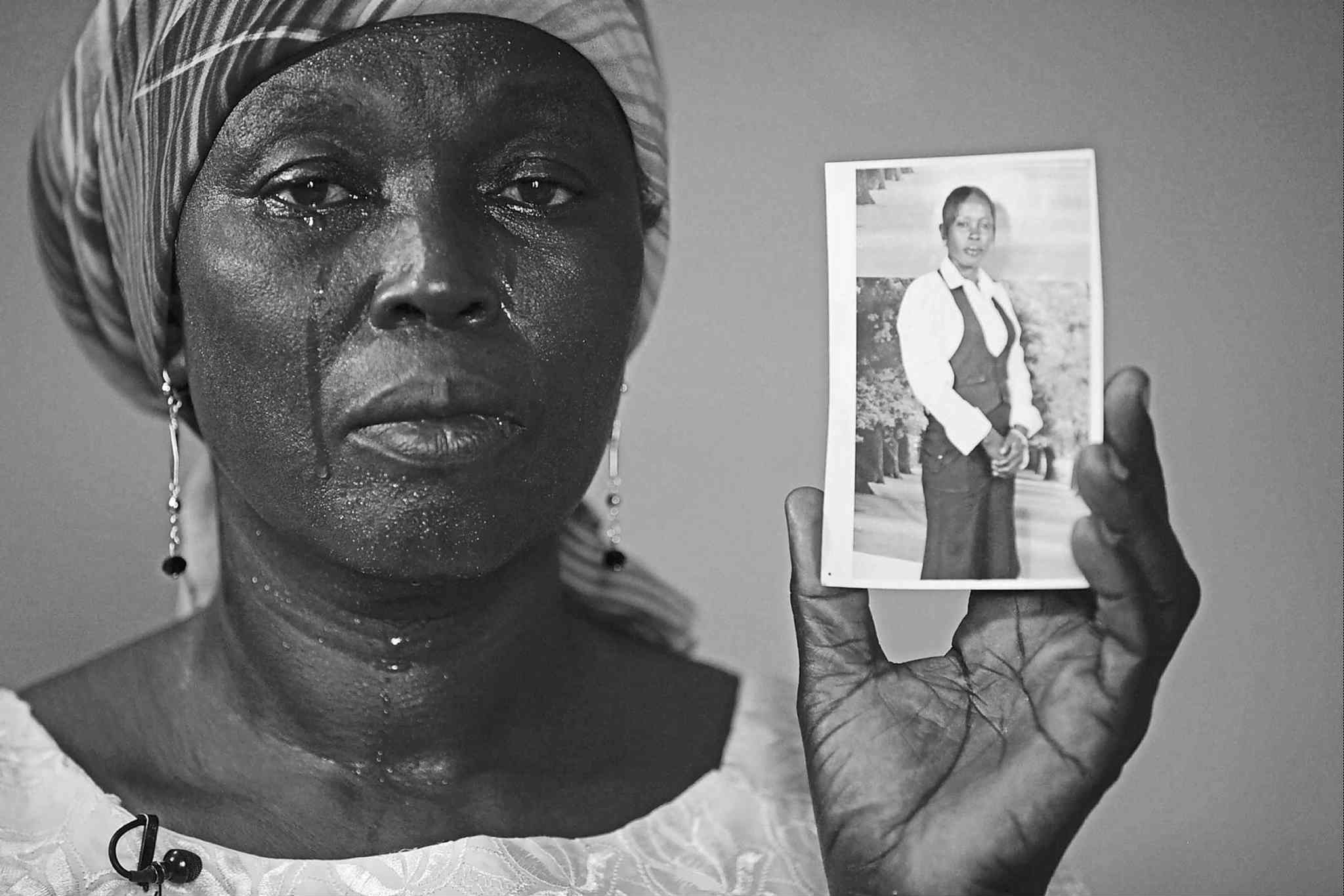 Martha Mark,  the mother of  kidnapped  schoolgirl Monica Mark, cries as she shows her daughter�s photo in Chibok, Nigeria.