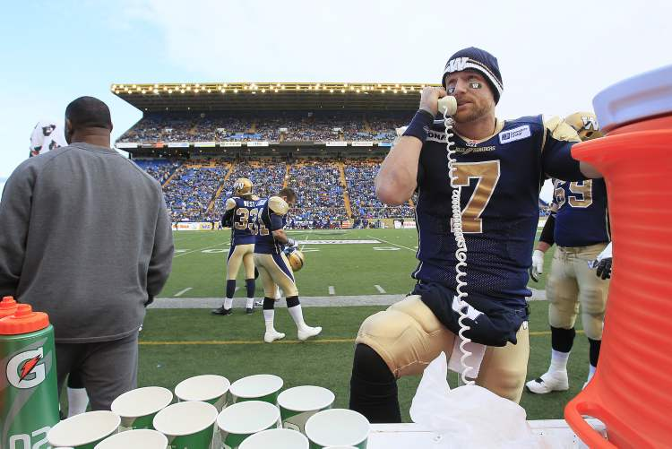 Winnipeg Blue Bombers' quarterback Alex Brink (7) on the phone to coaches during the first half of their CFL game against the Montreal Alouettes in Winnipeg on Saturday. (John Woods / The Canadian Press)