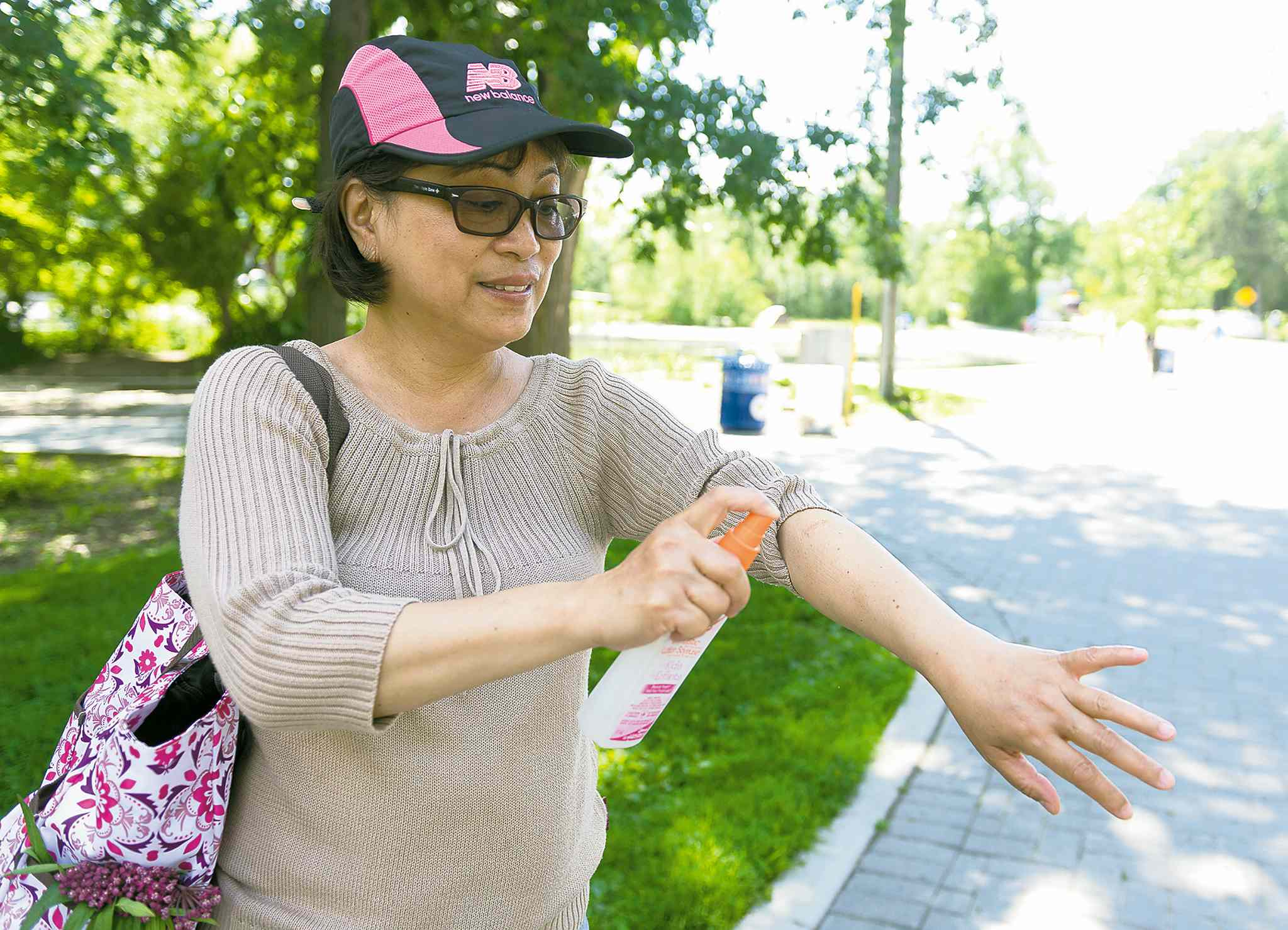 Emmellie Velasco sprays herself with mosquito repellent in Assiniboine Park on Saturday.