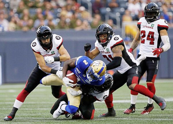 Winnipeg Blue Bombers Kenbrell Thompkins gets hauled down by Ottawa Redblacks' Avery Williams during the first half of CFL action in Winnipeg Friday, August 17, 2018.