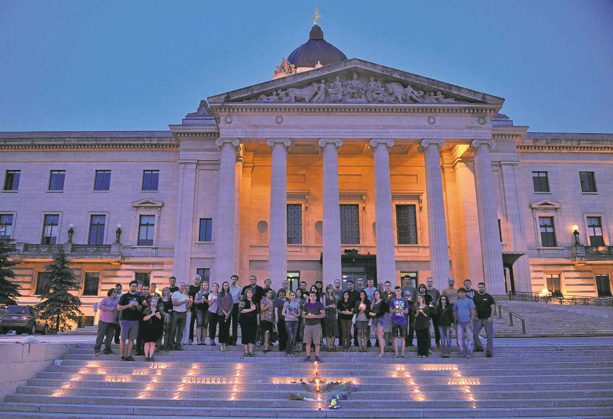 People gather on the steps of the Manitoba legislature Thursday night to participate in a candlelight vigil for the victims of flight MH17.