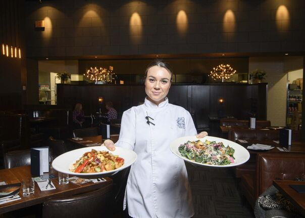 <p>Earls Polo Park head chef, Danelle Diaferia, serves dishes of Hunan Chicken Kung Pao and Warm Kale Salad .</p>