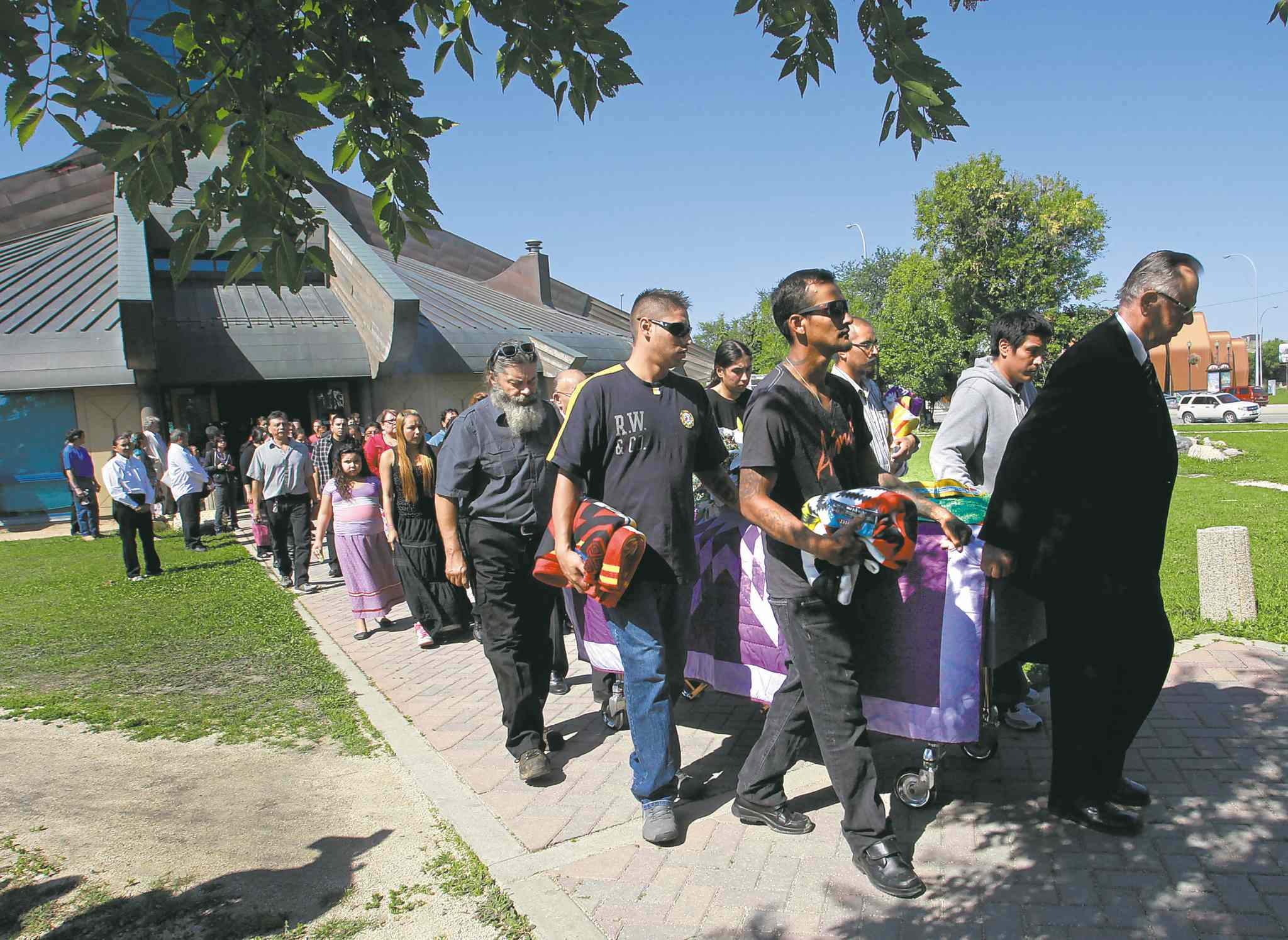 Mourners take part in the procession from Thunderbird House after the funeral for Faron Hall.