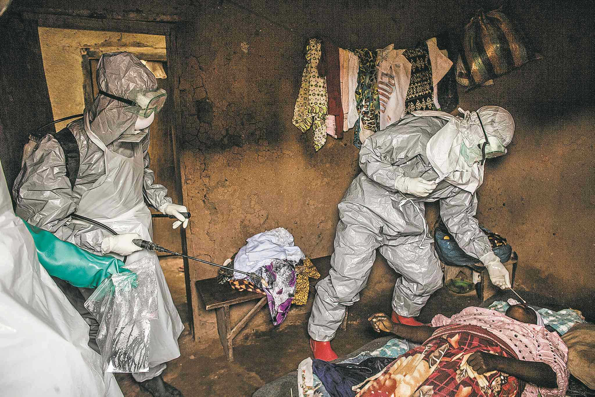 Members of a Red Cross burial team take samples from the body of a woman they suspect died of Ebola in the village of Dia, Sierra Leone.