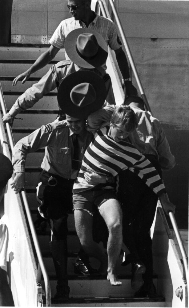 Bruce Decker, 17, is carried away by RCMP after making a run for the stairs where the Beatles had just greeted fans at Winnipeg International Airport on Aug. 18, 1964.