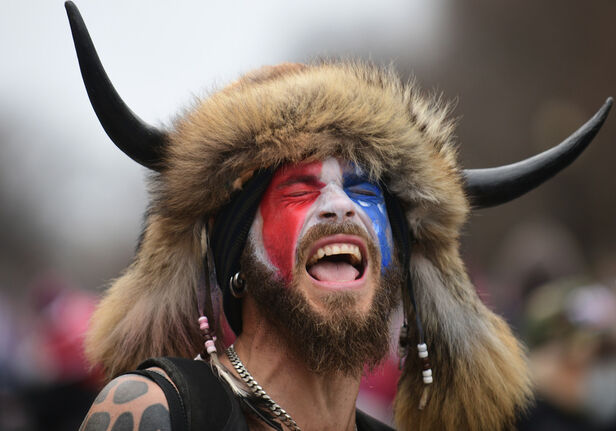 Jake Angeli stormed the Capitol building wearing buffalo horns, raccoon fur, face paint, feathers, beads and a spear. (Astrid Riecken / The Washington Post files)