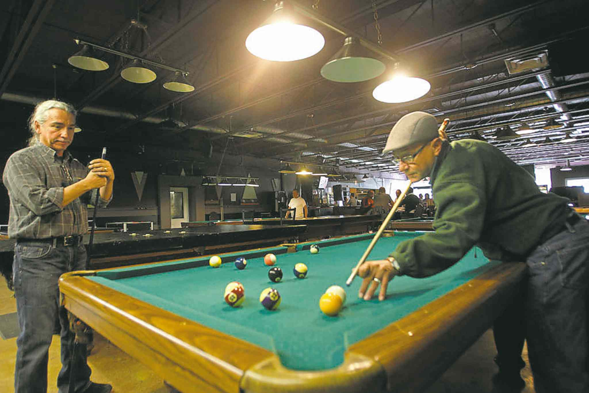 Terry Malazdrewich (right) and Richard  Armstrong shoot some pool.