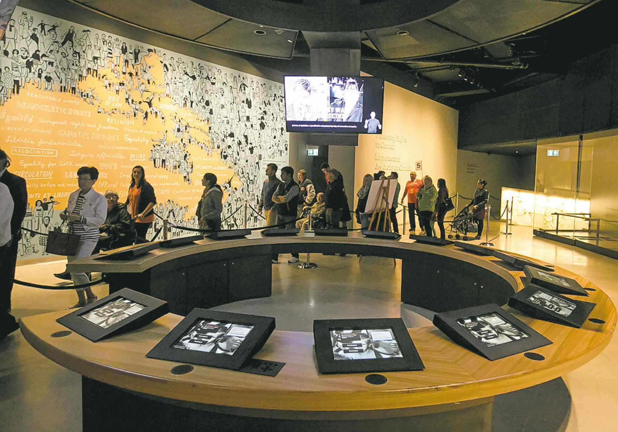 CMHR visitors file through the Protecting Rights gallery.