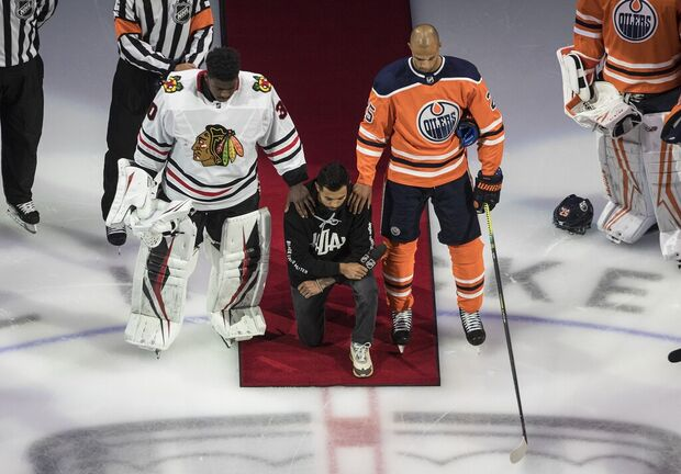 Minnesota Wild's Matt Dumba takes a knee during the national anthem flanked by Edmonton Oilers' Darnell Nurse, right, and Chicago Blackhawks' Malcolm Subban before an NHL playoff game in Edmonton on Aug. 1. No other players on either team knelt with Dumba.
