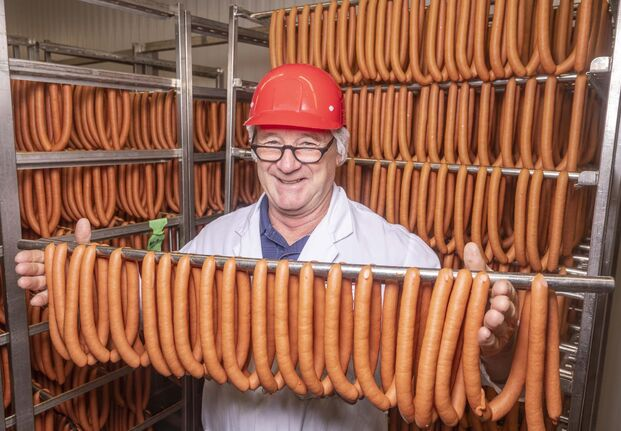"SASHA SEFTER / WINNIPEG FREE PRESS</p><p>Winnipeg Old Country Sausage owner Ken Werner stands among some of the 24,000 ""world-famous wieners"" the company produces daily.</p>"