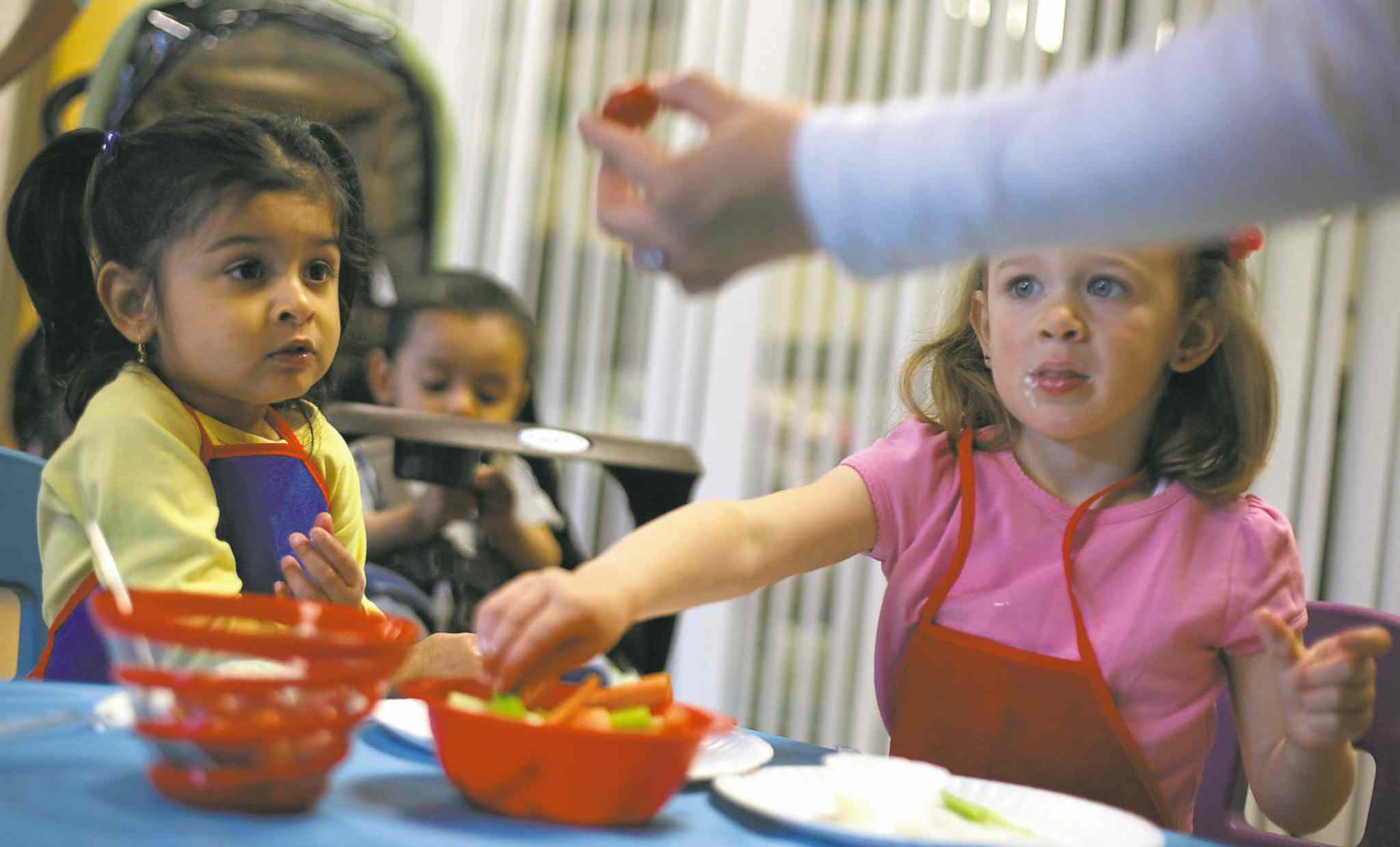 Sakina Vohra, 2, and Tatum Groves, 2, learn how to dip vegetables in ranch dressing during a cooking class.