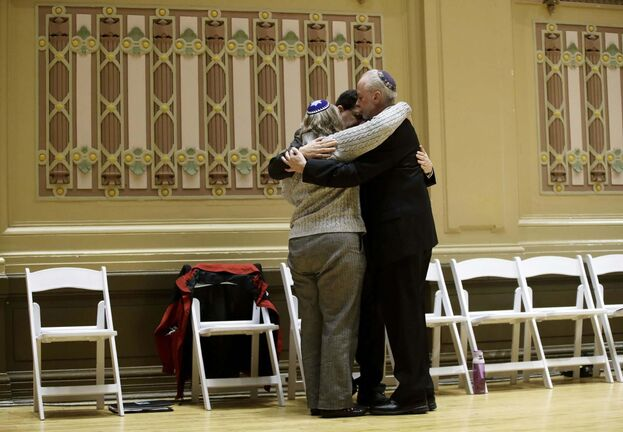 Mourners embrace at a gathering in the aftermath of the shooting at the Tree of Life synagogue in Pittsburgh. (Matt Rourke / The Associated Press)