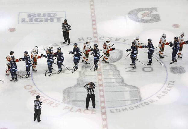 The Calgary Flames and the Winnipeg Jets shake hands following NHL qualifying round game action in Edmonton, on Thursday August 6, 2020. THE CANADIAN PRESS/Jason Franson</p>